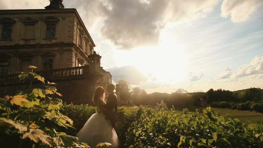 Loving groom kisses his beautiful bride at the sunset. Magnificent antique castle under cloudy sunset sky as background - HD stock video clip