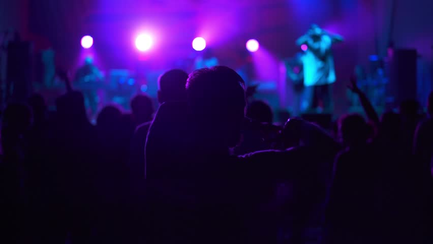 crowd enjoying night perfomance of musicians, hands up - 4K stock video clip