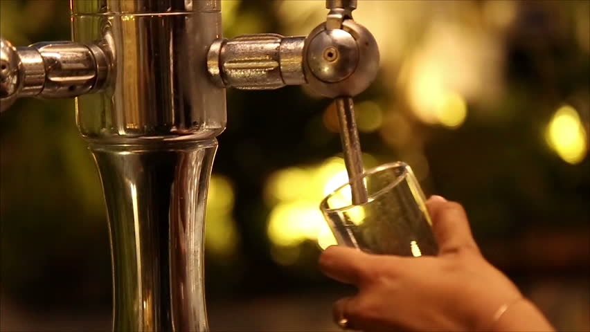Barmaid filling a glass of beer in slow motion