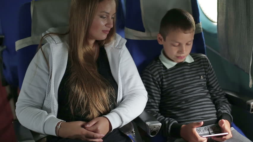 Mother and son are flying in an airplane - HD stock video clip