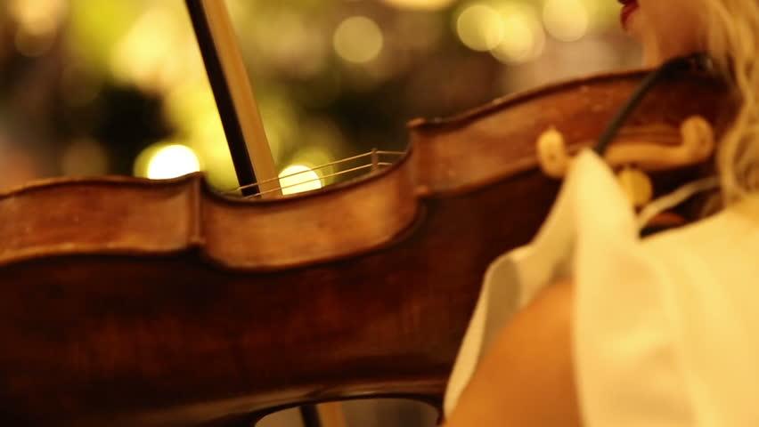 Young woman play violin.