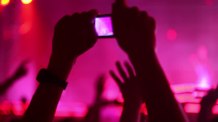 Hands hold camera with digital display among people at rave party with pink red light, view from behind - HD stock video clip