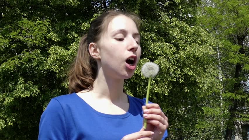 Young Girl Blowing on a Dandelion. the Action in Slow Motion. - HD stock video clip