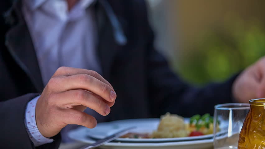 A man is in the middle of his meal. His fork and a knife are leaning on a plate and he is talking with the woman that is sitting opposite him in a restaurant. Close-up shot. | Shutterstock HD Video #18085555