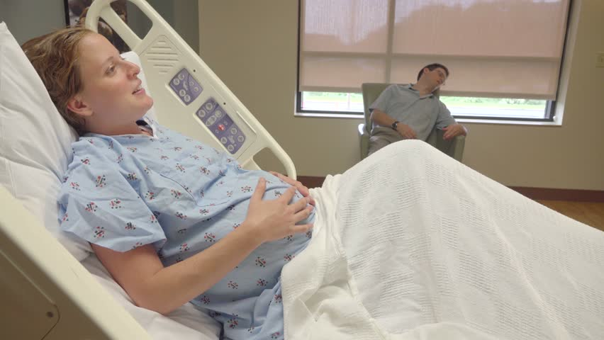 Pregnant wife trying to wake up sleeping husband in hospital - 4K stock footage clip