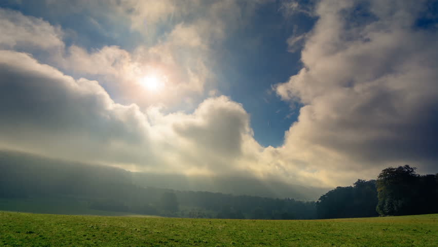 Timelapse footage of moving clouds and the rays of sunlight falling through them onto a green meadow - HD stock footage clip
