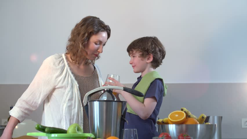 Young Caucasian Mother and Child Homemade Fresh Orange Juice and Drink it