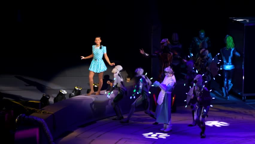 """ST. PETERSBURG, RUSSIA - JANUARY 2, 2016: Brothers Zapashny circus, """"UFO. Alien Planet Circus"""" show in Saint Petersburg. Aliens around the amused human young girl in blue dress."""