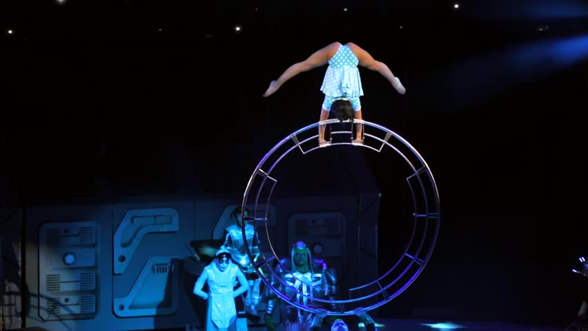 """ST. PETERSBURG, RUSSIA - JANUARY 2, 2016: Brothers Zapashny circus, """"UFO. Alien Planet Circus"""" show in Saint Petersburg. Woman gymnast does tricks on the big wheel that is holded by an alien"""