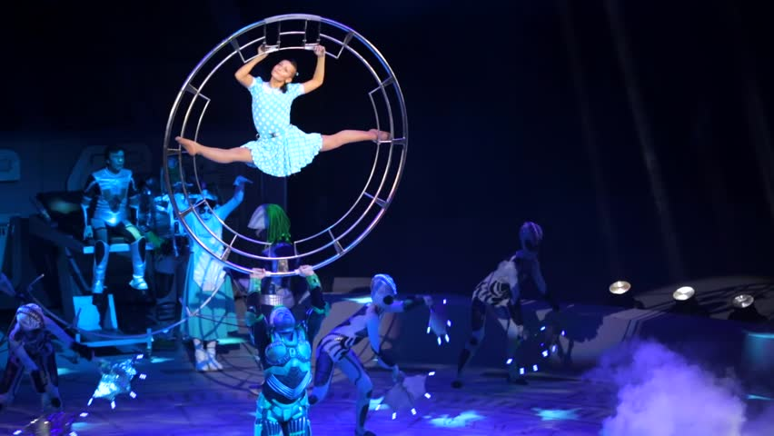 """ST. PETERSBURG, RUSSIA - JANUARY 2, 2016: Brothers Zapashny circus, """"UFO. Alien Planet Circus"""" show in Saint Petersburg. Alien lifts a big wheel with gymtast in it. Girl does leg-split"""