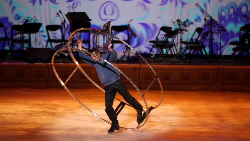 """MOSCOW, RUSSIA - JANUARY 12, 2016: Full rehearsal of theater of ice miniatures perfomance anniversary program """"We are 30"""" under direction of I.Bobrin. Man performs with big wheel on ice showing tricks"""