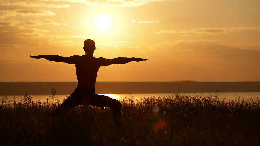 Silhouette of young sportive man practicing yoga at sunset. Slow motion. - HD stock footage clip