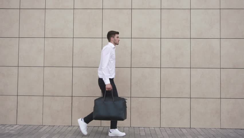 Young confident businessman walking on the background of the office wall. The modern businessman concept.