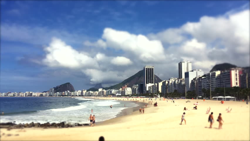 Clouds build over a scenic time lapse view of Copacabana Beach shore from the Leme end with the city skyline of Rio de Janeiro, Brazil