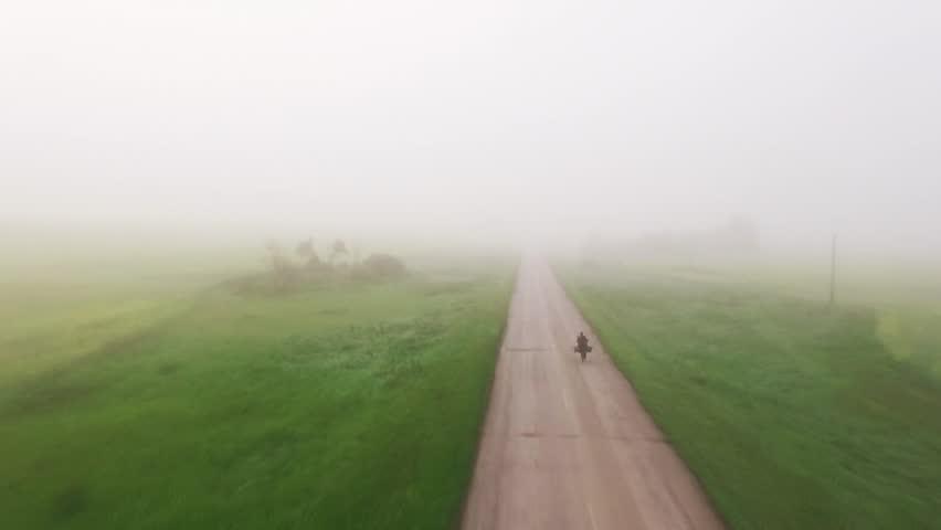 Cycling person along morning foggy road