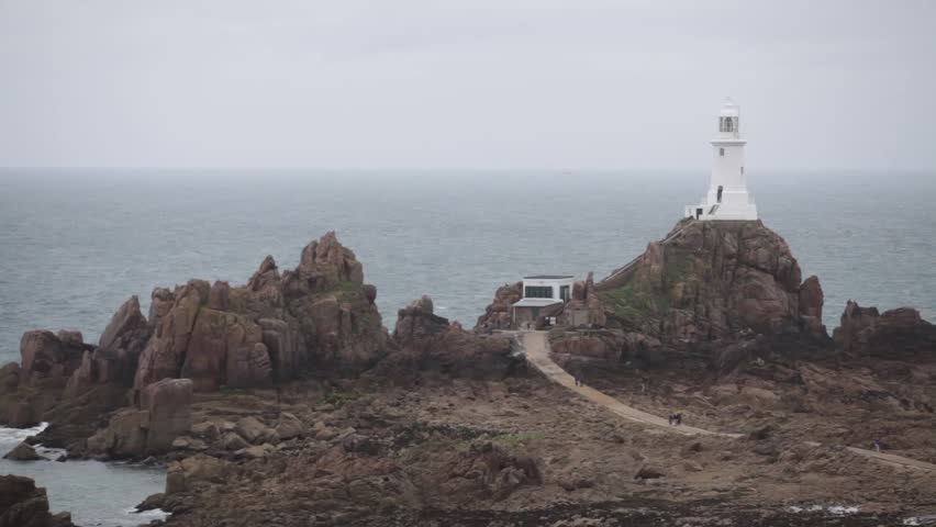 View of a lighthouse on Jersey island, with unrecognizable people walking by.
