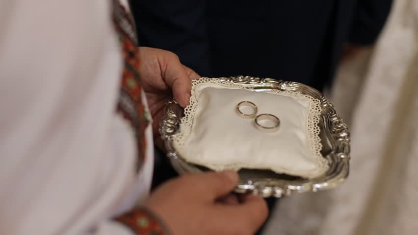 Close up of luxurious rings on plate in the church. Wedding ceremony