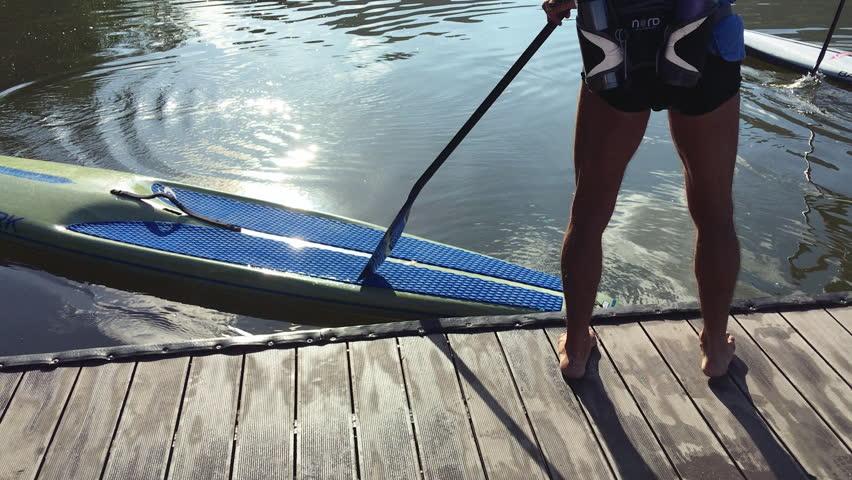 RIO DE JANEIRO - MARCH 14, 2016: Brazilian paddle boarder steps from the dock onto his board for a morning practice session on Lagoa Rodrigo de Freitas Lagoon.
