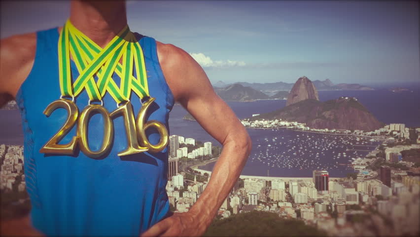 First place athlete wearing 2016 gold medals standing at a scenic overlook with Sugarloaf Mountain and Guanabara Bay in Rio de Janeiro, Brazil