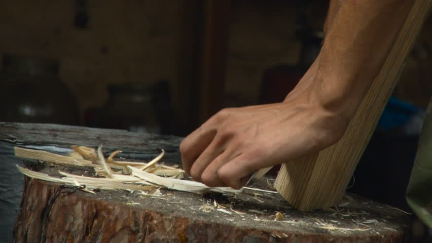 Whittling a Piece of Wood With a Knife. Stump, Hands, Shaving, Work. Closeup
