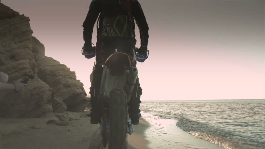 Off-road motorbike rides on a sandy beach in the early morning   Shutterstock HD Video #18307549