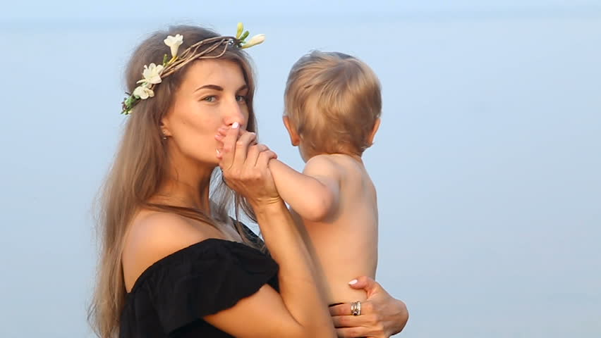 mother in a black dress and a wreath, holding in the hands of his son on the beach