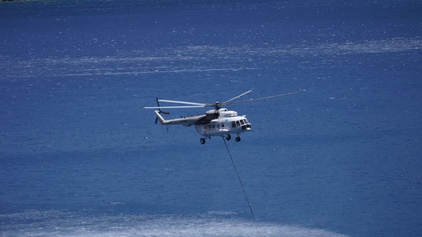 Helicopter firefighter take water in the sea