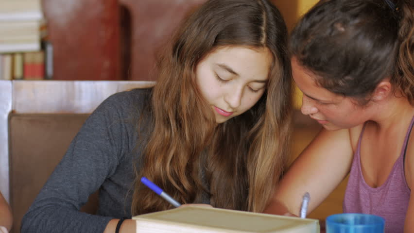 Cute teenage girls work on homework together and laugh and have a good time