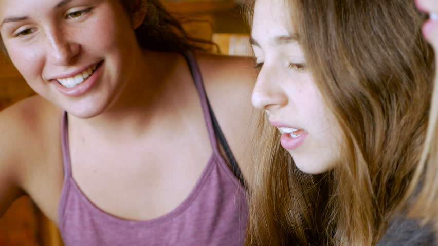 Three beautiful teenage girls sit next to each other collaborating - handheld in a modern home