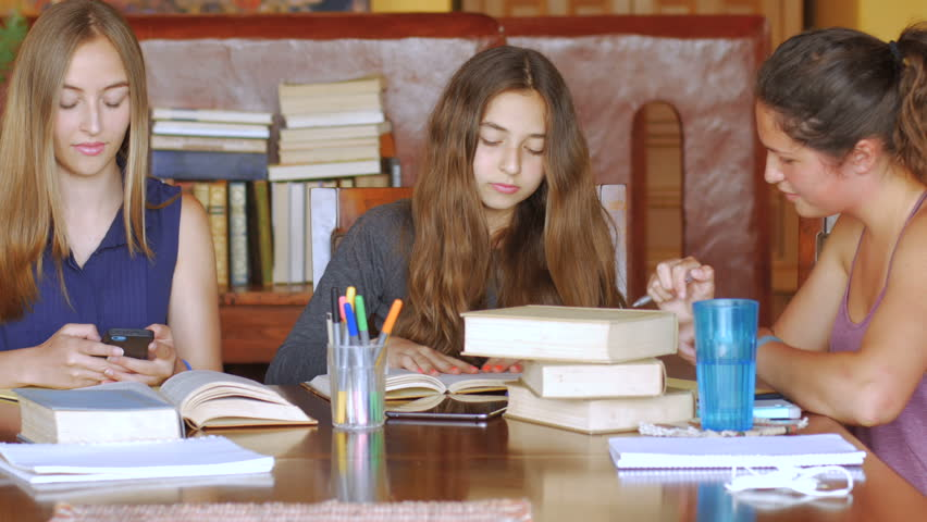 An attractive teen shares her phone with her friends while studying at a modern home surrounded by books