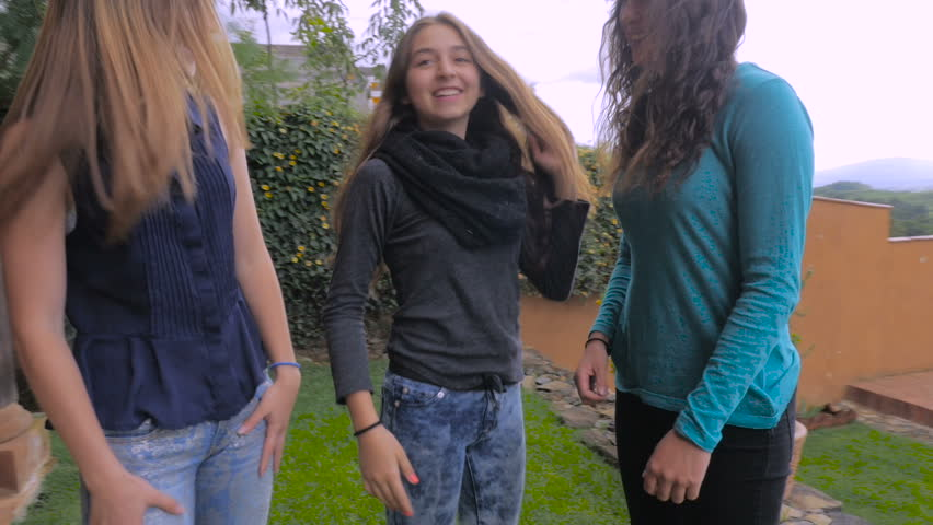Hand held of three teenage girls dancing outside having fun and one falls to the ground laughing in slowmo