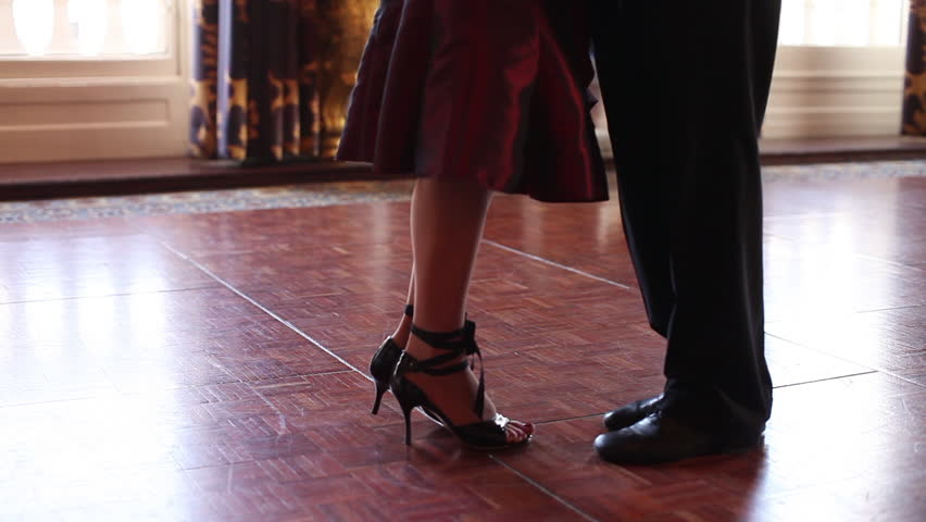 Tango dancing couple's feet moving across a polished floor - HD stock video clip