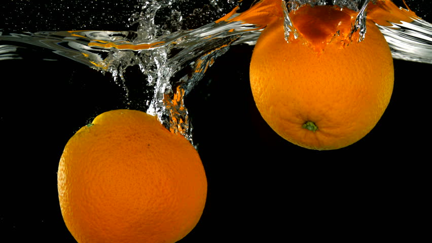 Slo-motion whole orange falling into water