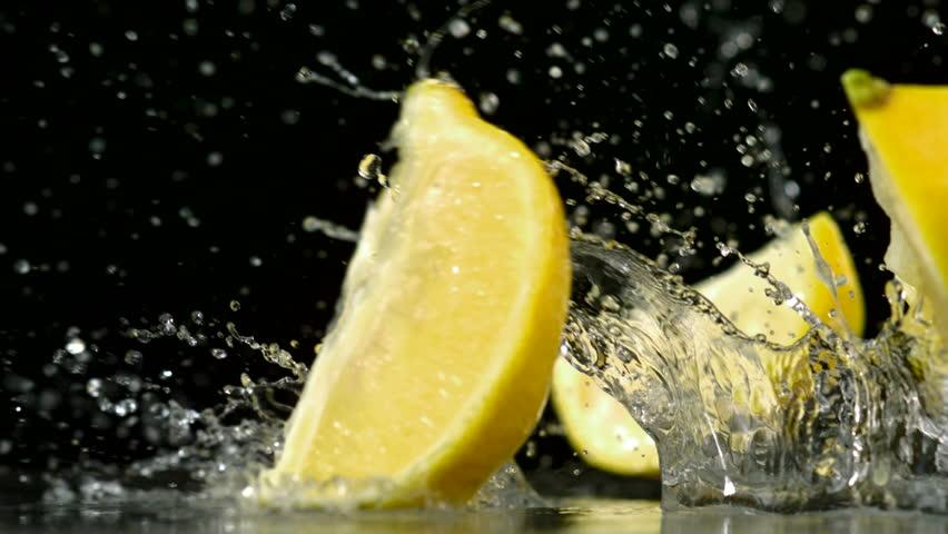 Slo-motion lemon  falling into wedges against black drop