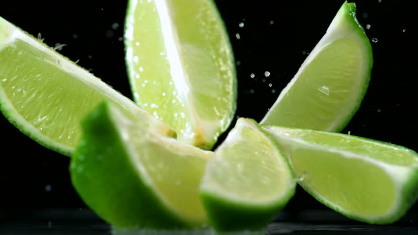 Slo-motion lime  falling into wedges against black drop