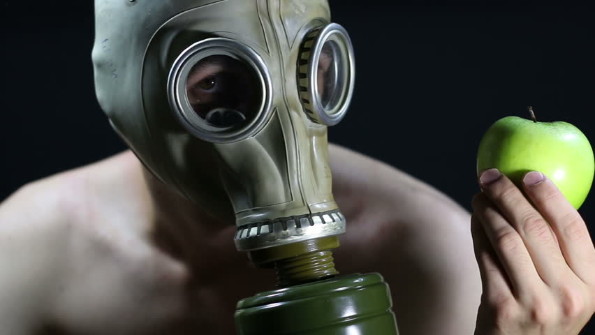 Naked man in a gas mask holding green Apple