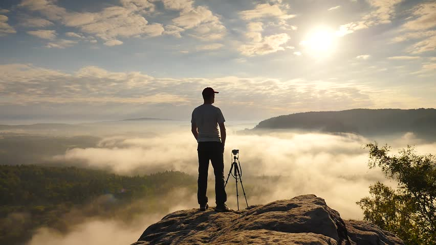 Photographer in grey t-shirt and red cap preparing tripod on cliff. Dreamy fogy landscape, blue misty sunrise in a beautiful valley below | Shutterstock HD Video #19017910