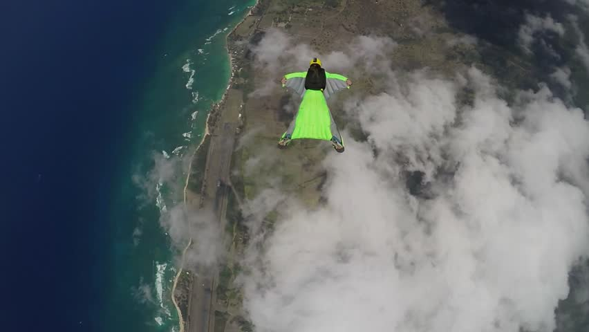 Lifestream men jumping with a wingsuit parachute over Hawaii, slow motion