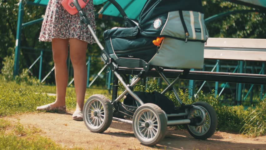 Mother in summer dress roll baby carriage and speaking on phone on street. Sunny. Motherhood | Shutterstock HD Video #19045936