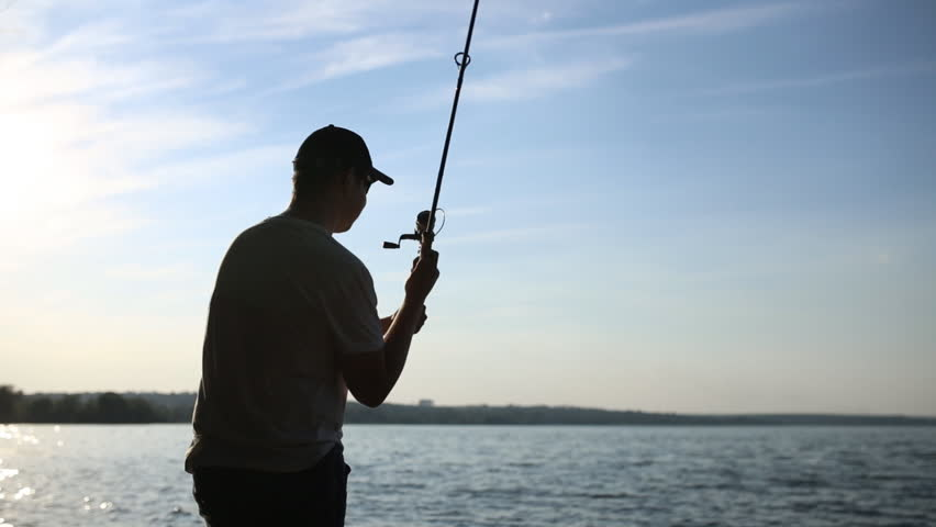 Silhouette of a fisherman who throws spinning at dawn | Shutterstock HD Video #19058149