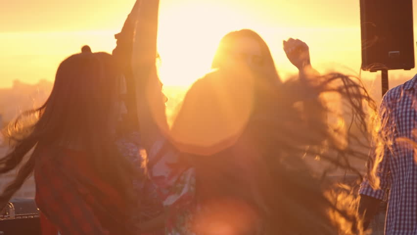 Group of multi-ethnic young people dancing to the music played by dj at sunset party on rooftop and raising arms with beer bottles up in the air | Shutterstock HD Video #19079326