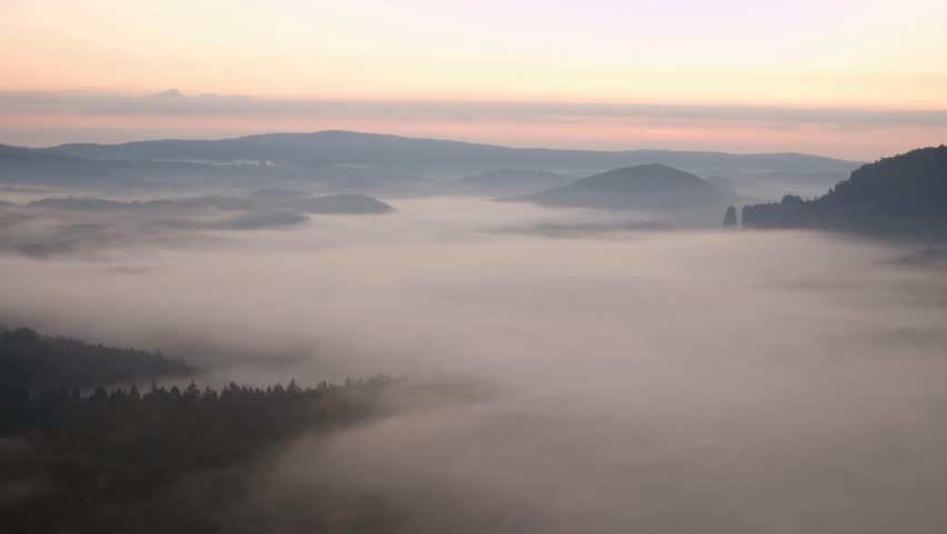 Marvelous misty morning in nature. Pink moment before daybreak in rocky hilly landscape. Sandstone peaks and treetops  increased from creamy fog, the fog blue or pink.The Sun appeared.  Time lapse  | Shutterstock HD Video #19153855
