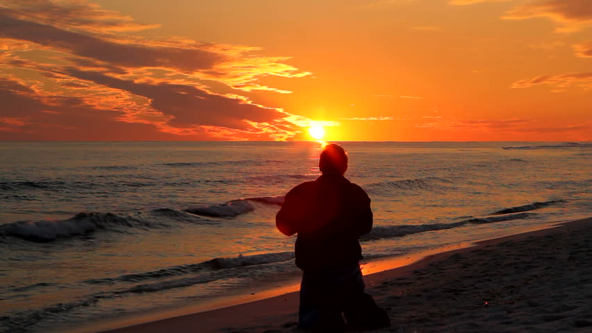 Man kneeling at the beach as the sun sets on the horizon and raises his arms in worship. - HD stock footage clip