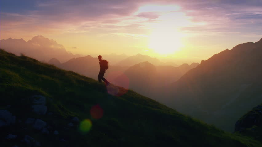 Aerial, edited - Epic shot of a man hiking on the edge of the mountain as a silhouette in colorful sunset | Shutterstock HD Video #19249192
