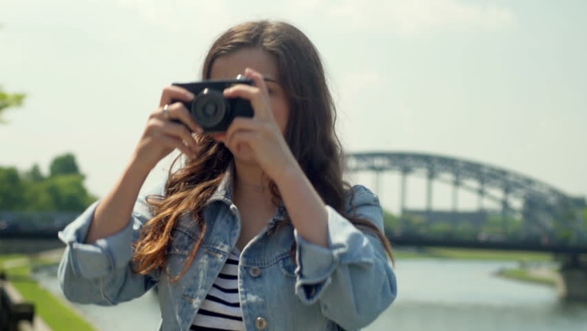 Young girl standing next to the river and doing photos on old camera    Shutterstock HD Video #19319815
