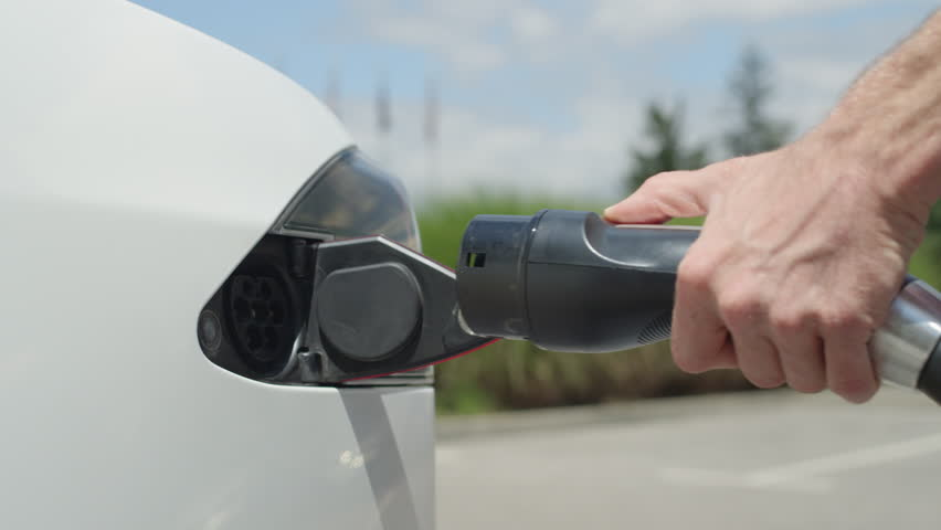 CLOSE UP, SLOW MOTION: Man plugging in electric car at super charging station. Luxury white electrical car recharging. Environmentally conscious man charging his electric vehicle | Shutterstock HD Video #19333837