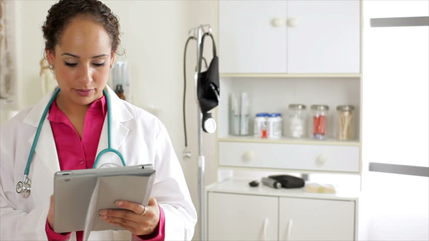 A pretty Hispanic physician working with an electronic tablet stops and smiles for the camera. - HD stock footage clip