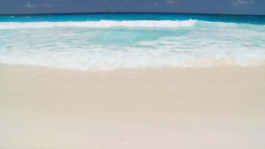 whitecaps landing on sandy beach at blue sky