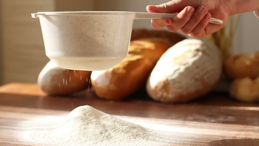 Hand sifts the flour through a sieve, slow motion - HD stock video clip