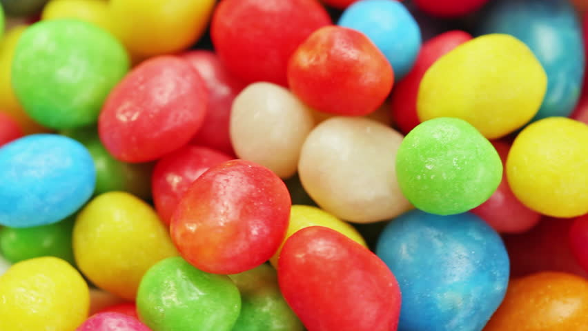 Multicolor bonbon sweets (ball candies) rotating food background, closeup view